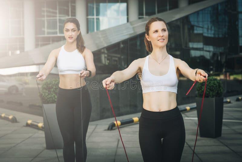 2 спортсмена женщин скача на прыгая веревочки в улице города Девушки тренируют outdoors Разминка, спорт, здоровый образ жизни стоковые фотографии rf