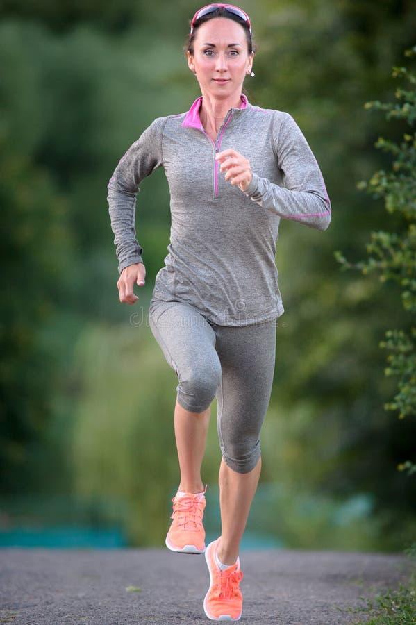 Спортсменка бежит причаливая крупный план стоковые фото