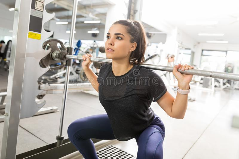 Спортсменка делая штангу сидит на корточках в спортзале стоковое изображение rf