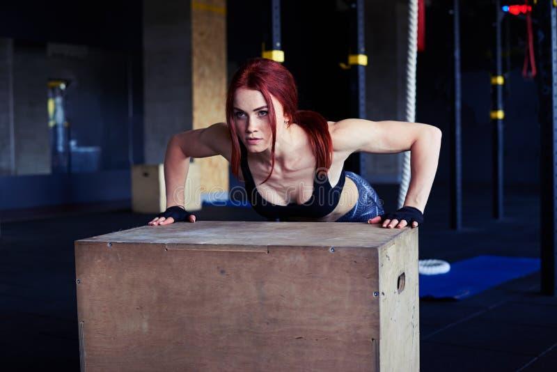 Спортсменка делать нажимает поднимает на деревянной коробке стоковые фотографии rf