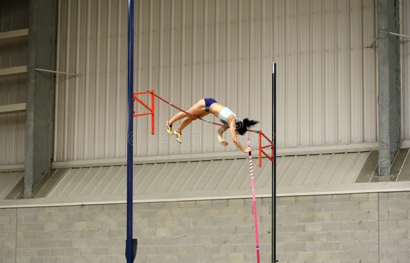 Спортсменка состязаясь в прыжке с шестом стоковое изображение