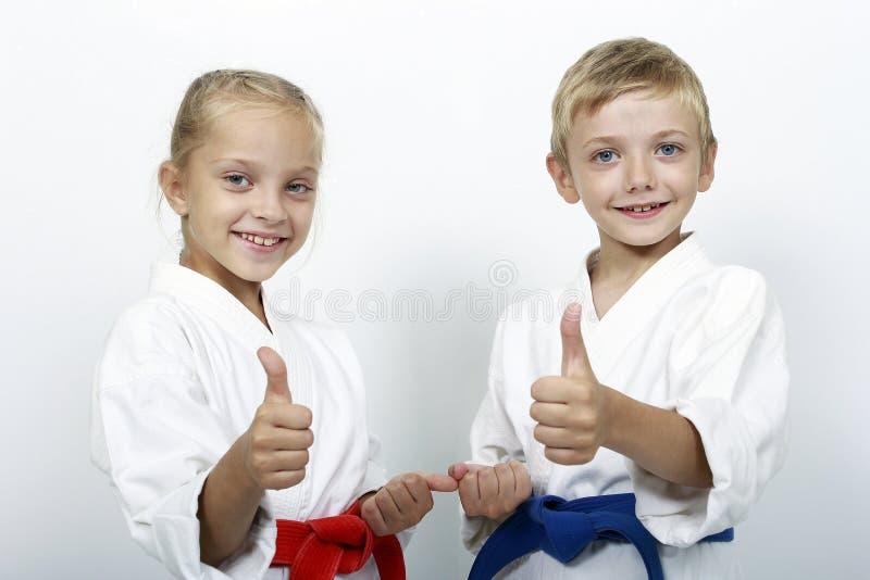 Спортсмены детей с поясами показывают большие пальцы руки вверх стоковые изображения