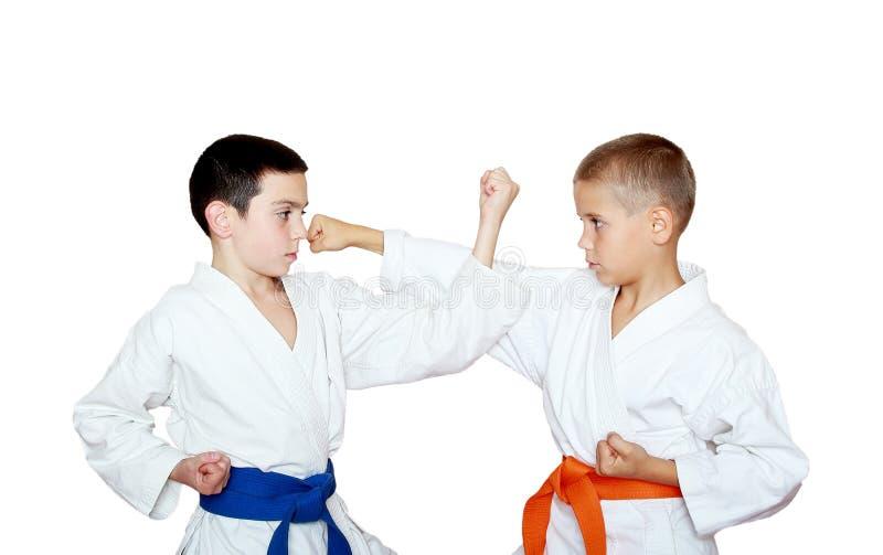 Спортсмены мальчиков с оранжевой и голубой тренировкой пояса спарили тренировки стоковое изображение rf