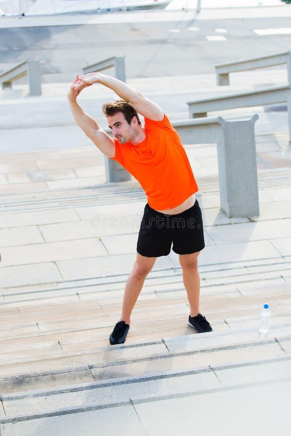 Спортсмены одели в футболке с космосом экземпляра для ваших бренда или рекламы протягивая мышцы рук перед тренировать outdoors стоковые изображения