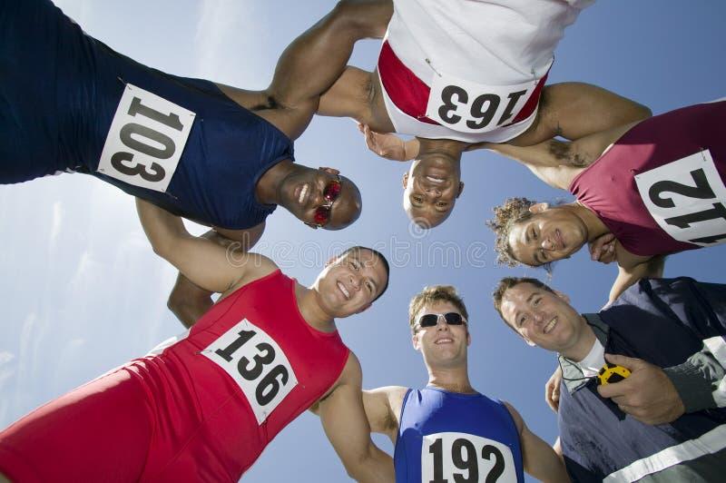 Спортсмены при тренер формируя груду стоковые фото