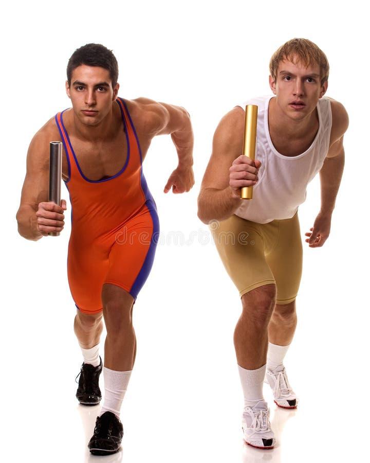Спортсмены участвуя в гонке реле стоковое фото rf