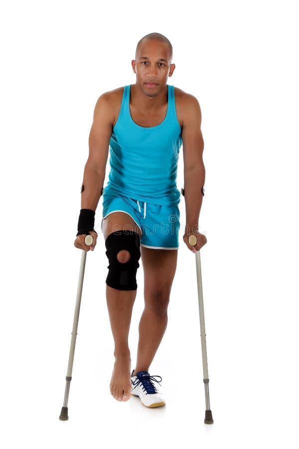 спортсмен афроамериканца crutches детеныши человека стоковая фотография
