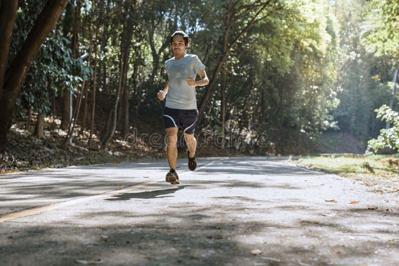 Спортсмен бегуна молодого человека бежать на ехал, в парке стоковое изображение