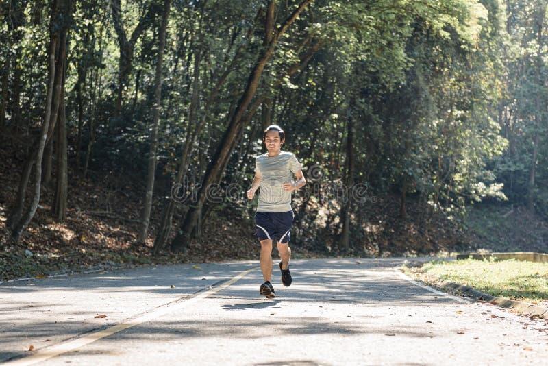 Спортсмен бегуна молодого человека бежать на ехал, в парке стоковые изображения