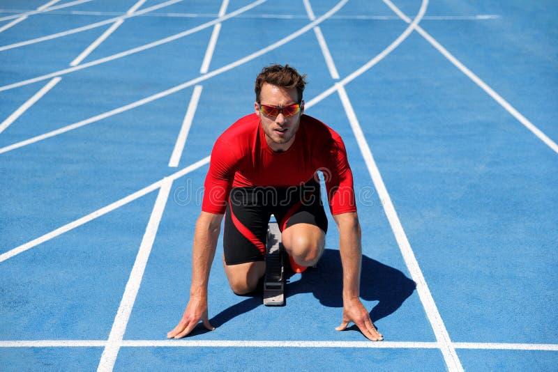Спортсмен бегуна начиная ход на начале, который побежали следа на голубых идущих следах на на открытом воздухе стадионе атлетики  стоковая фотография