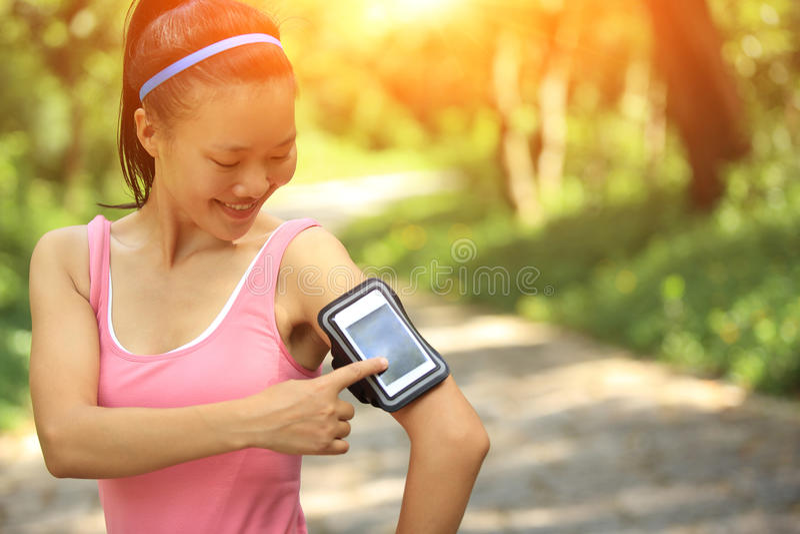 Спортсмен бегуна слушая к музыке в наушниках от умного mp3 плэйер телефона стоковое изображение rf