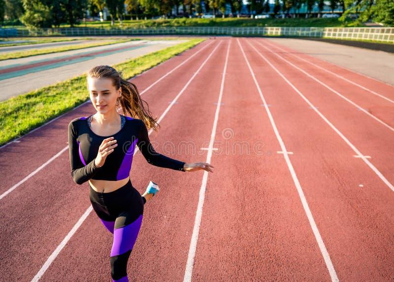 Спортсмен девушки бежит на стадионе на заходе солнца стоковое фото