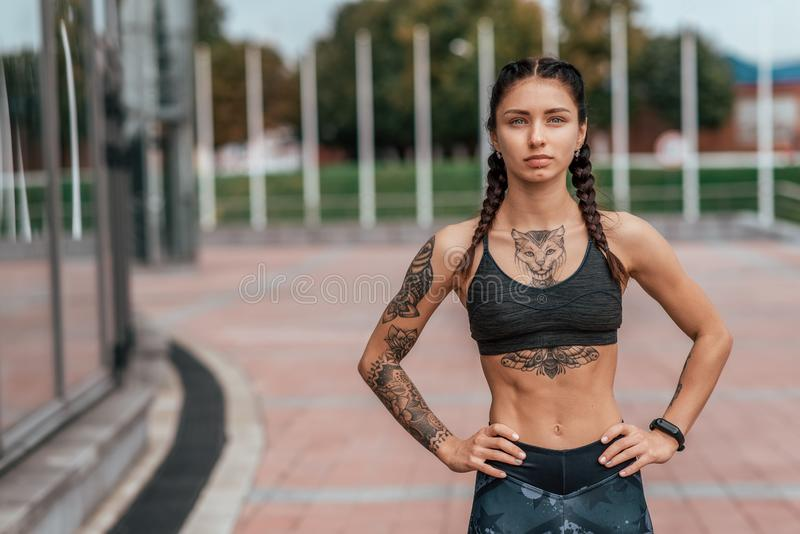 Спортсмен девушки, город лета Отдыхать после игры спорт на улице В гетры и купальнике татуирует женщину стоковое фото rf