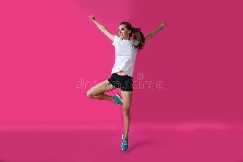 Спортсмен девушки представляя на розовой предпосылке стоковое фото