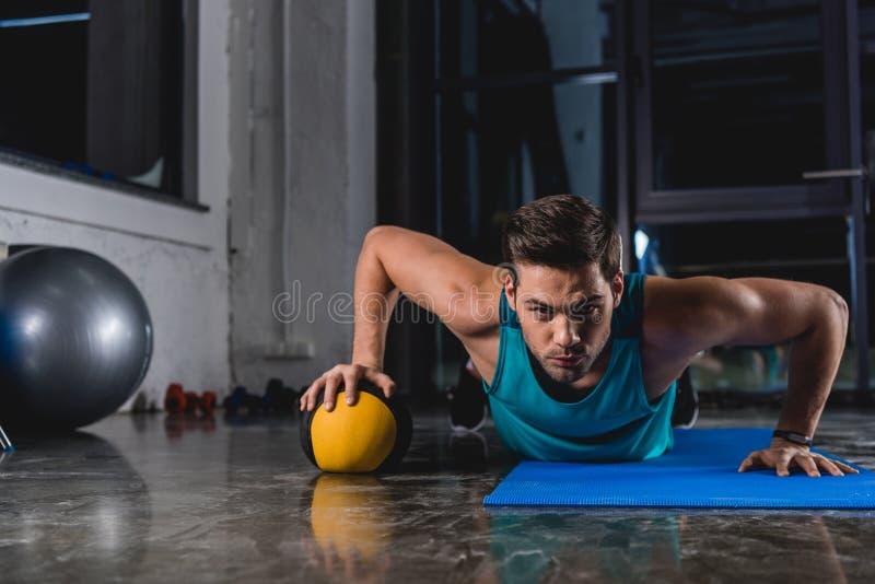 спортсмен делать нажимает поднимает с шариком медицины на циновке йоги стоковое фото rf