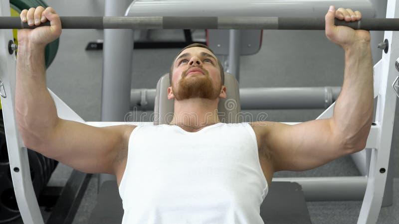 Спортсмен делая стенд штанги отжимая пока работающ на фитнес-клубе Мышечный человек работая в спортзале стоковые фото