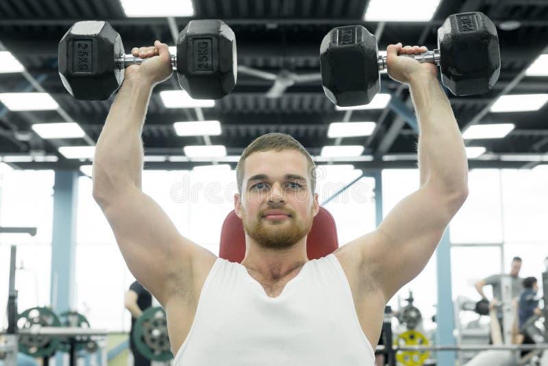Спортсмен делая тренировку для плеч при гантели сидя на стенде Молодые мышечные поезда человека на спортзале стоковые фото