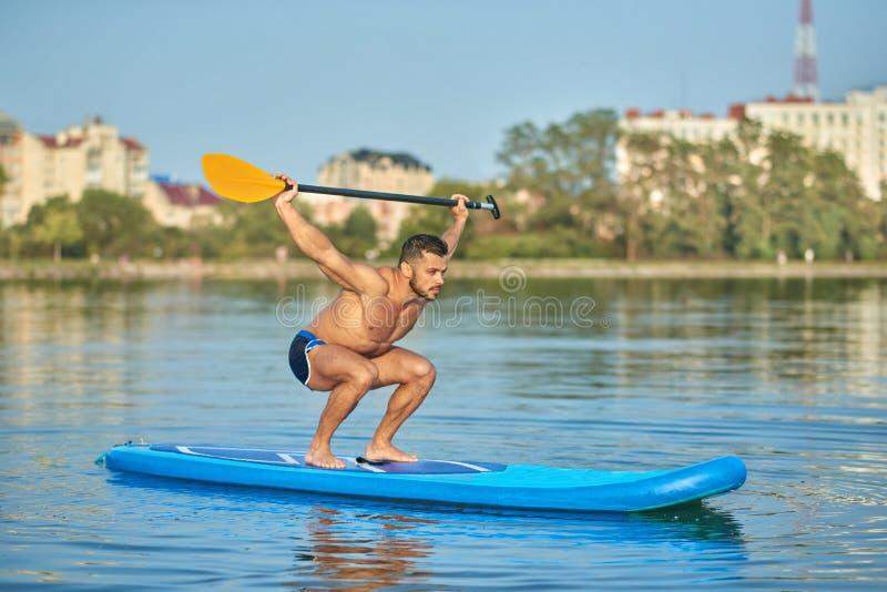 Спортсмен держа длинное весло надземный, плавающ на доске затвора в озере города стоковое изображение