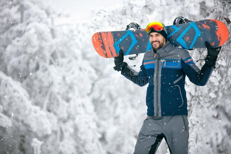 Спортсмен держа доску и возвращение лыжи от местности катания на лыжах стоковые фотографии rf
