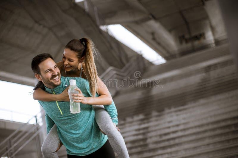 Спортсмен держа спортсменку на его задней части и имея потеху стоковая фотография rf
