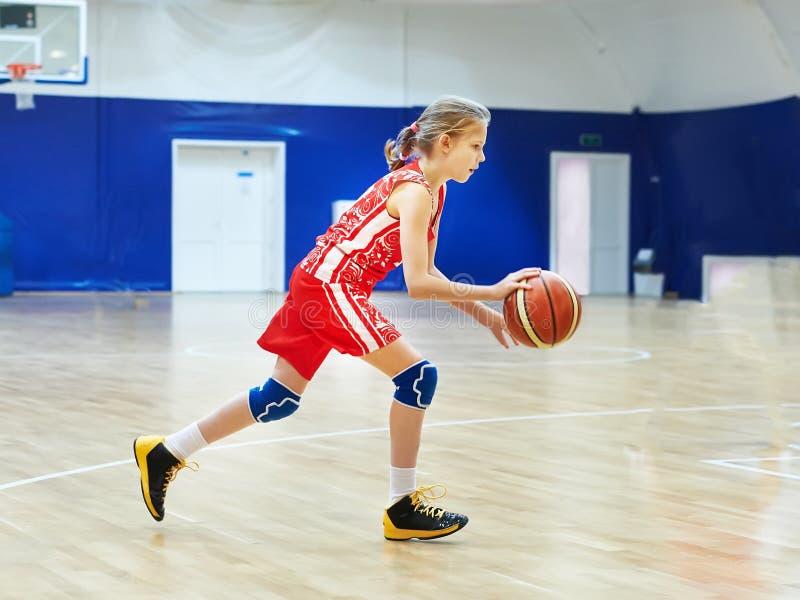 Спортсмен девушки в форме играя баскетбол стоковое фото rf