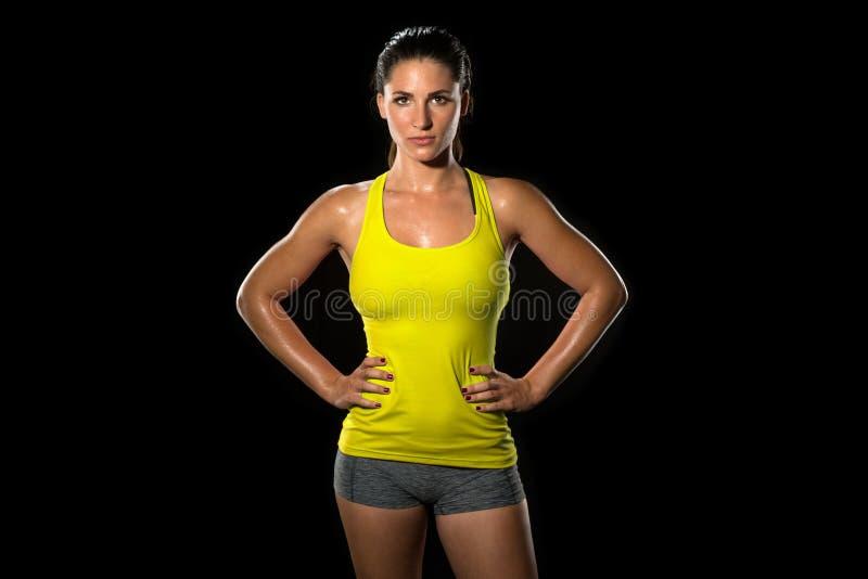 Спортсмен женского тела привлекательной пригонки тонкий тонкий тонизированный изолированный на черноте стоя уверенно женщина пред стоковое изображение rf