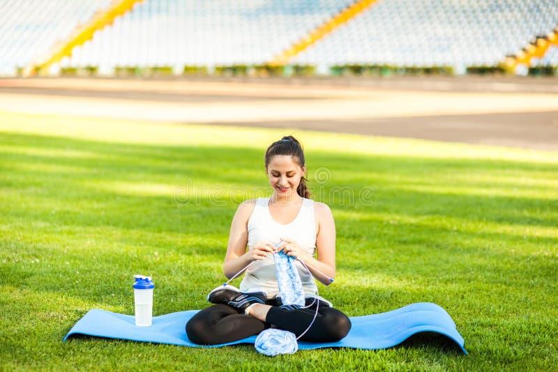 Спортсмен женщины вязать свитер на футбольном поле стоковое изображение rf