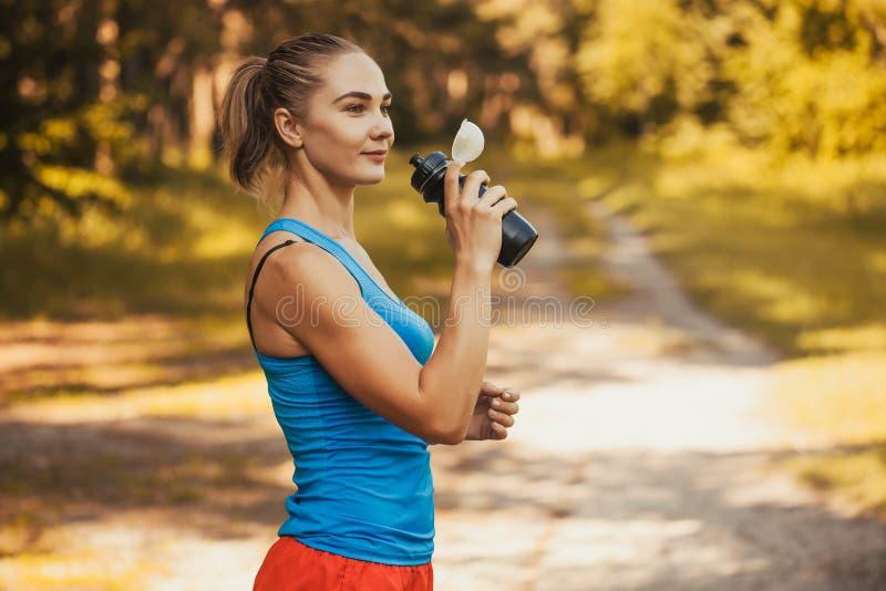 Спортсмен женщины принимает перерыв, она выпивая стоковое изображение