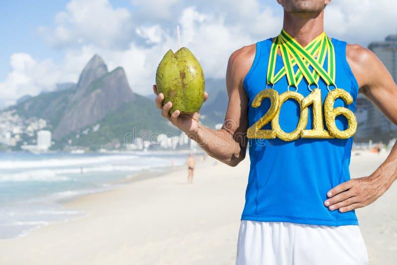 Спортсмен 2016 золотой медали держа кокос Рио стоковые изображения