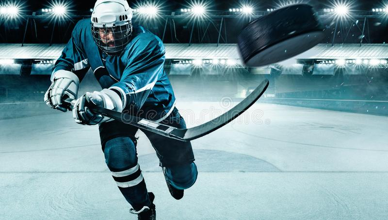 Спортсмен игрока хоккея на льде в шлеме и перчатки на стадионе с ручкой Съемка действия r стоковое изображение