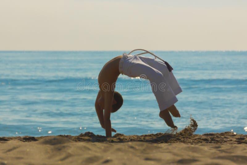 Спортсмен мальчика на пляже стоковые изображения rf