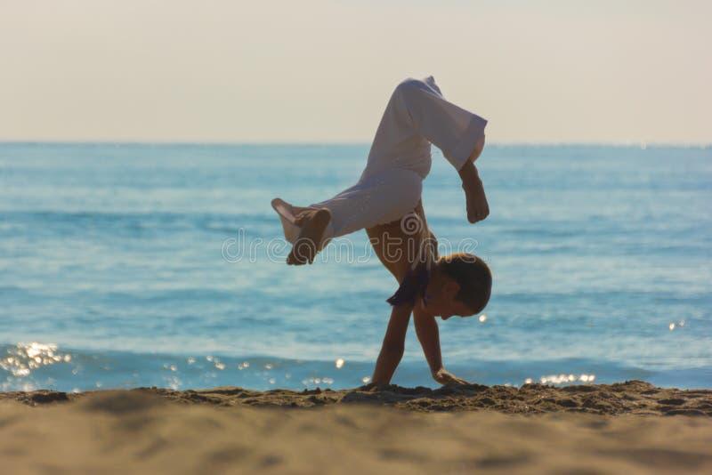 Спортсмен мальчика на пляже стоковое изображение