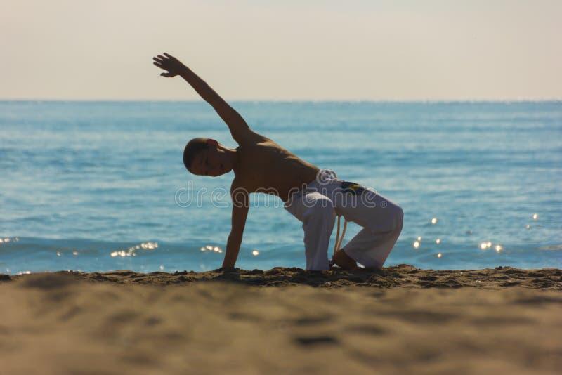 Спортсмен мальчика на пляже стоковое изображение rf