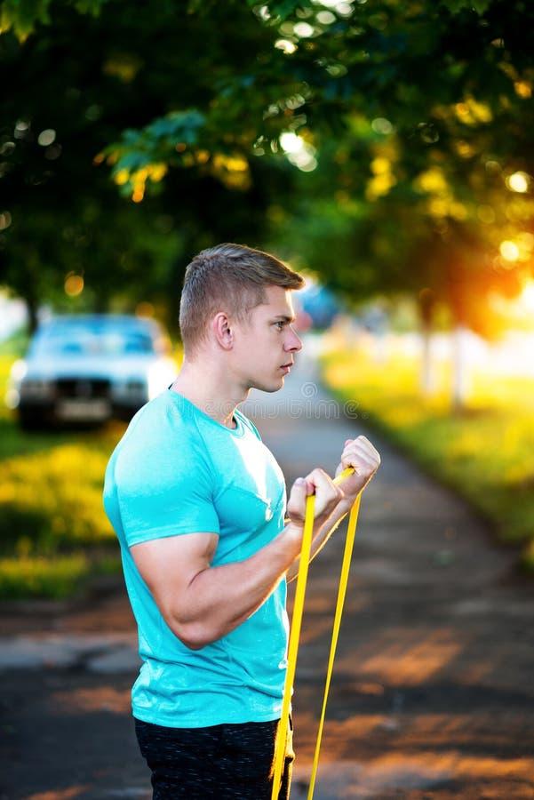 Спортсмен нагревает с эластичными резиновыми лентами тренировки, outdoors природой Тренер спортсмена в футболке Образ жизни лета стоковое изображение