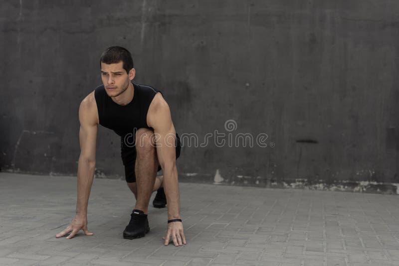 Спортсмен начиная его спринт на серой промышленной предпосылке стены стоковая фотография rf