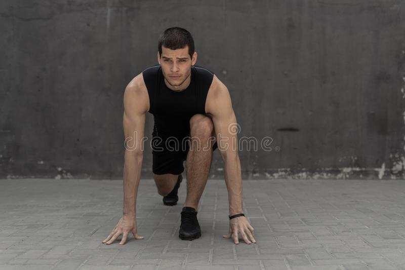 Спортсмен начиная его спринт на сером промышленном backgrou стены стоковая фотография
