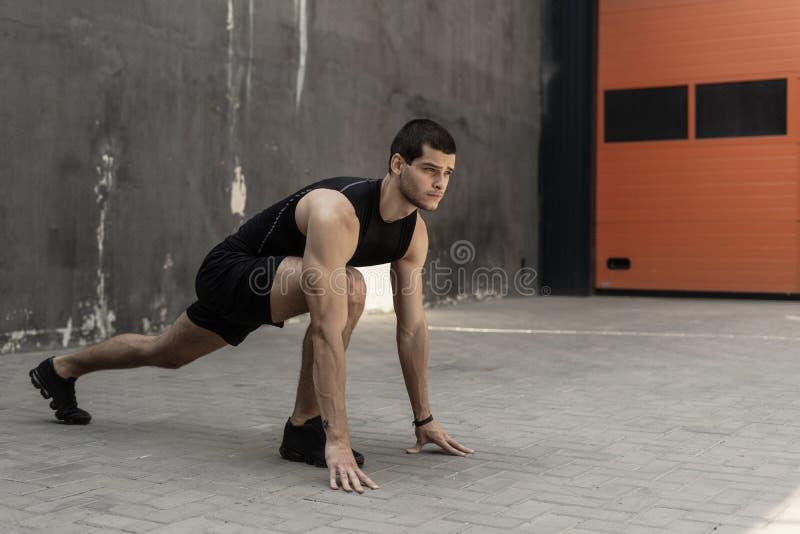 Спортсмен начиная его спринт на сером промышленном backgrou стены стоковое изображение