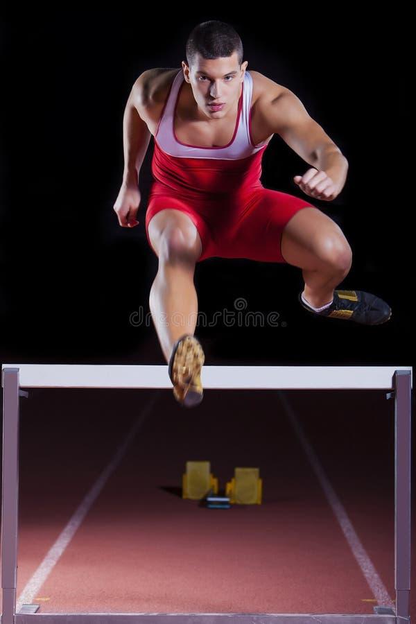 Спортсмен на барьере в легкой атлетике стоковые фотографии rf