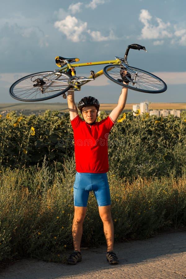 Спортсмен поднял велосипед над его головой Нося спорт зацепляют, шлем и стекла r стоковое изображение rf