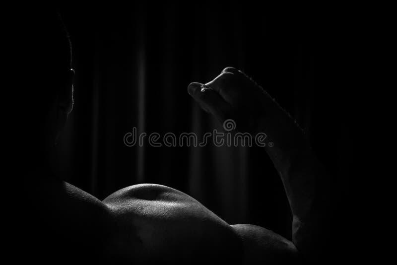 Спортсмен показывает нагнетенный конец-вверх руки на черной предпосылке занимаясь культуризмом г-н Олимпия стоковое изображение