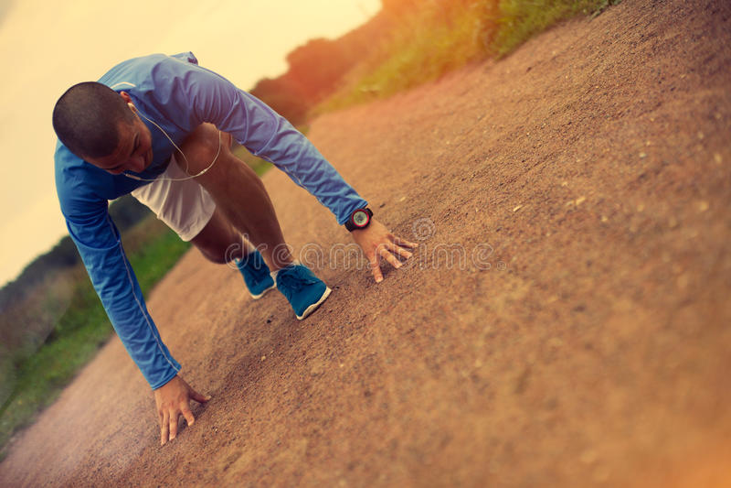Спортсмен при наушники подготавливая начать стоковая фотография rf