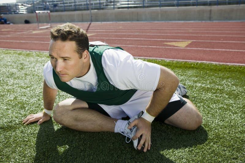 Спортсмен протягивая на следе стоковые фотографии rf