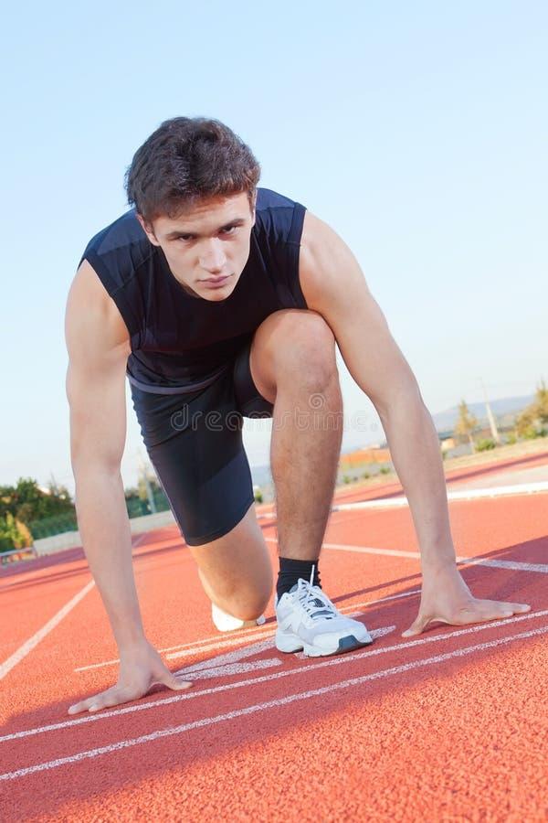 спортсмен решительно подготавливает старт к стоковое фото