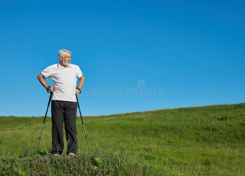 Спортсмен стоя с отслеживать вставляет на зеленом холме стоковое изображение
