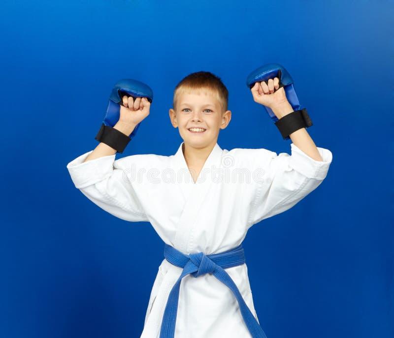 Спортсмен с голубыми верхними слоями на руках радуется победа стоковое фото