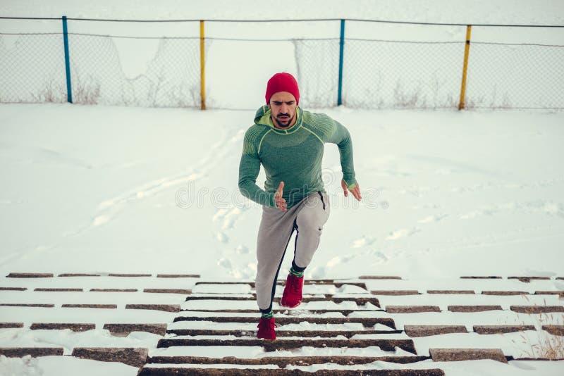 Спортсмен с красной шляпой и красными тапками бежать вверх снежные лестницы стоковые фото
