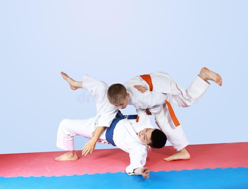 Спортсмен с оранжевым поясом бросил спортсмена с голубым поясом стоковое фото rf