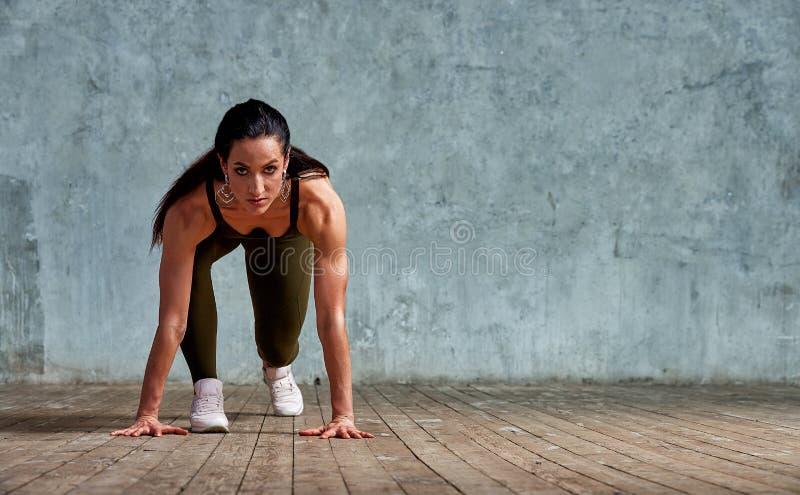 Спортсмен фитнеса в начале против стены подготавливая для спринта Фитнес, здоровая концепция образа жизни r стоковые фотографии rf