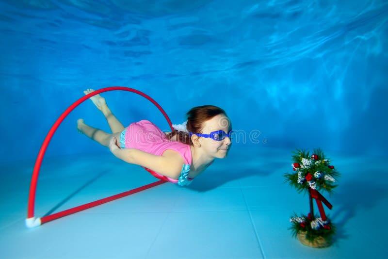 Спорт детских игр подводные Пикирования и заплывы через обруч на дне бассейна стоковые изображения