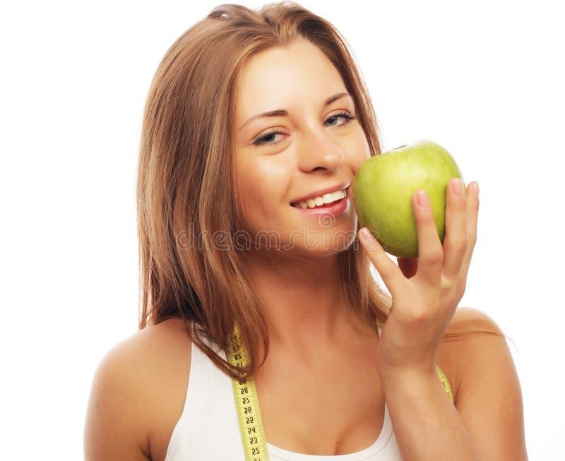 Спорт, диета, здоровье и концепция людей: Молодая жизнерадостная женщина в спорт носит с яблоком, изолированным над белой предпос стоковые фото